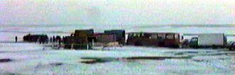 l'équipe du film dans la plaine. on remarque les cars transportant les figurants et les camions de materiel.